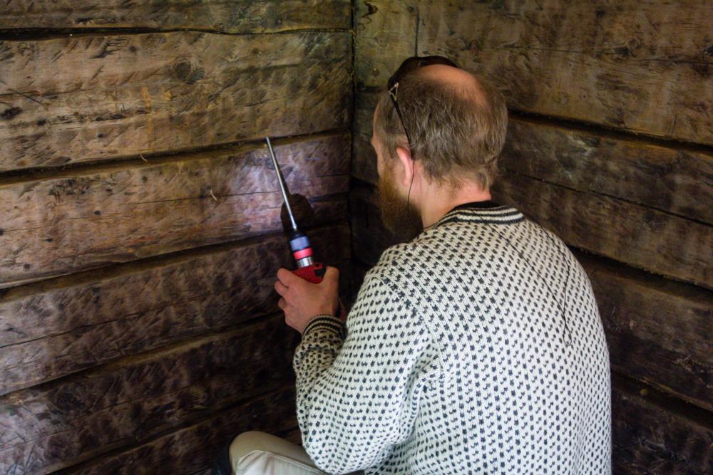 Roger Persson tar dendrokronologisk prøve fra en tømmervegg.