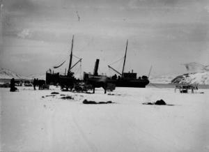 Fjordene var ofte islagt og derfor måtte båten legge til iskanten langt fra land og losse og laste der. Her legger båten til iskanten ute i Bøkfjorden, ca 1900. Foto: Ellisif Wessel, Grenselandmuseets fotosamling.