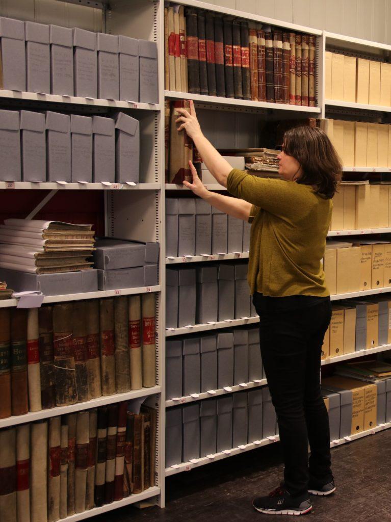 Varangerarkivers arkivar setter en eldre innbundet bok inn i en hylle med arkivmapper og andre bøker. Foto.