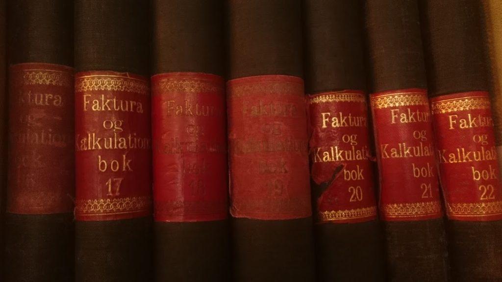 """Ryggene på 7 oppstilte eldre bøker merket """"Faktura og Kalkulation"""" nr 16-22. Foto."""