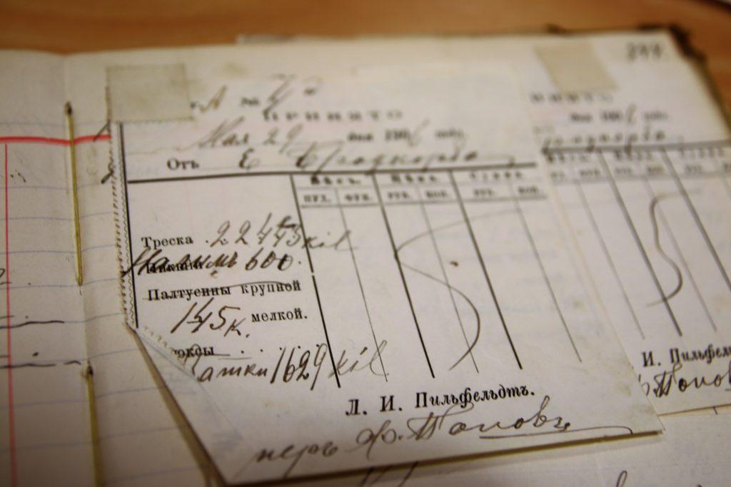 Side fra en gammel skrivebok som hvor det er limt inn kvitteringer med tekst på russisk. Foto.