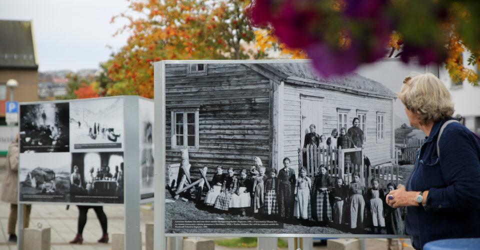 Link til side om Utstilling på Kirkenes torg. Bildet viser en kvinne som ser på utstillingen med svart-hvitt foto på et uteområde med trær og bygninger rundt. Foto.