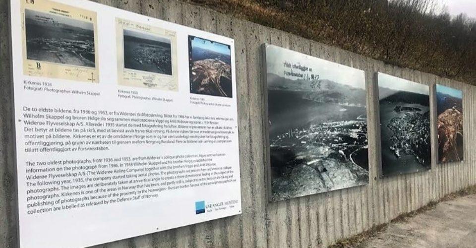 Link til side om utstilling av flyfoto i Kirkenes. Bildet viser plakater med flyfoto som henger på en murvegg utenførs. Foto.