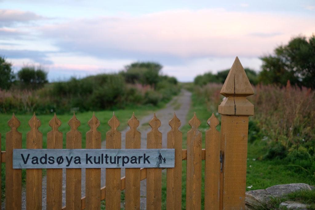 """Okermalt port foran en grusvei i et grøntområde. På porten er det et skilt hvor det står """"Vadsøya kulturpark""""."""
