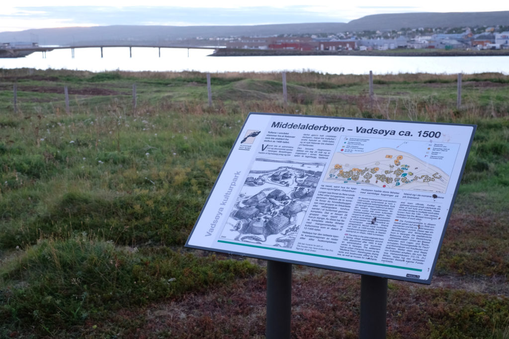 """Skilt som med synlig overskrift """"Middelalderbyen - Vadsøya ca. 1500"""" og utydelig tekst under. Med illustrasjon av middelalderbyen og kart over tuftefelt. I bakgrunnen ser man noen hustufter bake et gjerde, og på avstand: Vadsøsundet, brua og deler av Vadsø sentrum."""