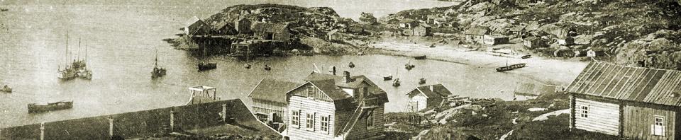 Viser et eldre foto i svarthvitt av en bukt med noen hus og fiskebåter.