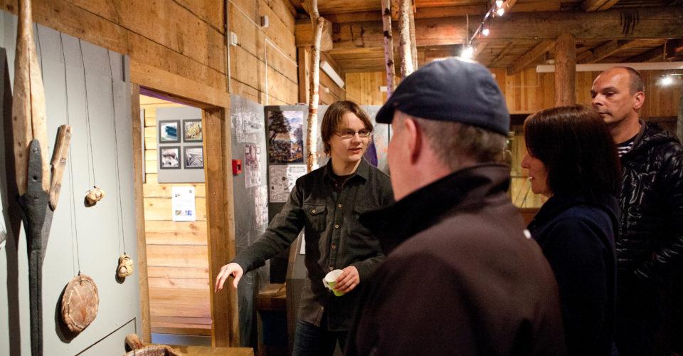 En ung mann viser fram gjenstander for en liten gruppe personer i en utstilling. Utstillinga er på Pomormuseet i Vardø.